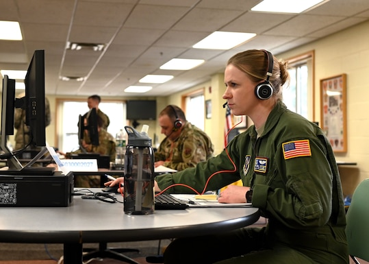 Staff Sgt. Mary Lux, boom operator, 133d Air Refueling Squadron, 157th Air Refueling Wing, New Hampshire Air National Guard, works the phones at a N.H. Employment Security call center at the Richard M. Flynn Fire Academy in Concord, April 2, 2020. The center fields thousands of calls a day in the wake of the COVID-19 crisis, and is staffed with 19 airmen on state active duty seven days a week, 13 hours a day. Photo by Staff Sgt. Charles Johnston, NHNG Deputy State PAO.