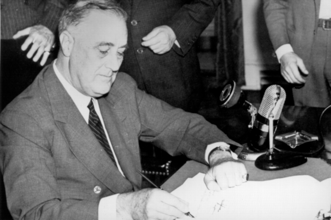 Seated man signs document.