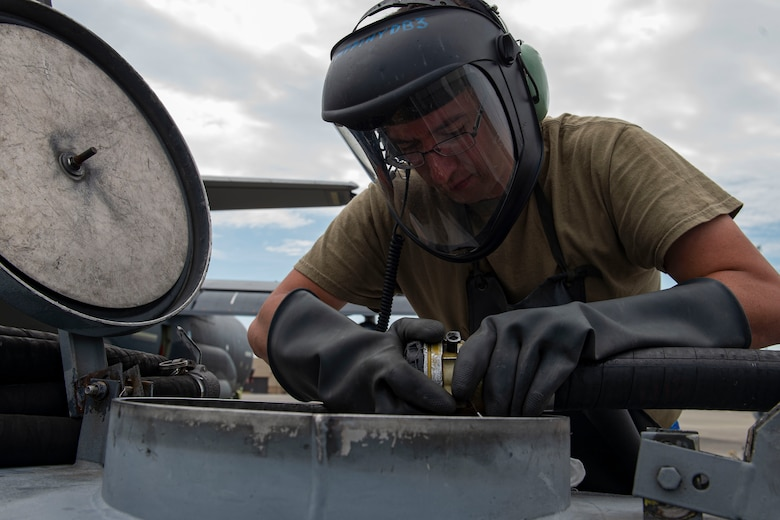 Photo of an Airman disconnecting an in-flight refueling hose.