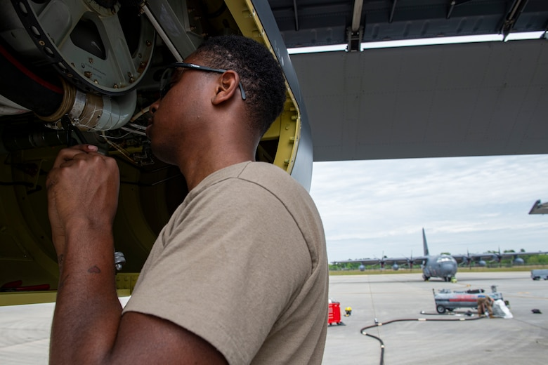 Photo of an Airman safety wiring a clamp for an in-flight refueling hose.