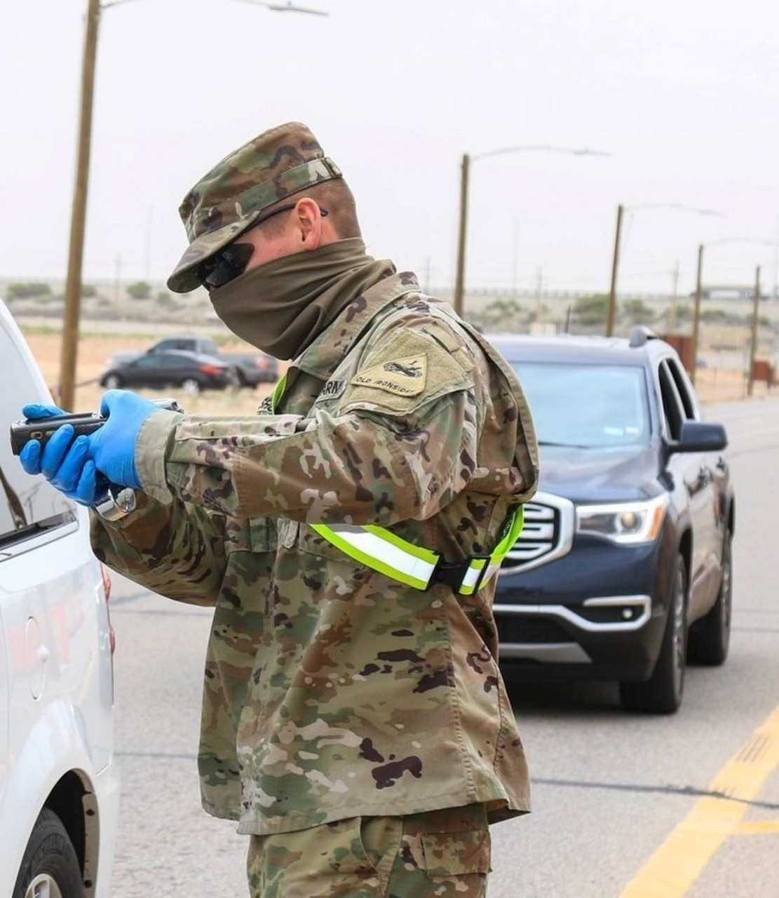 Soldier wears a face mask and gloves as protection.