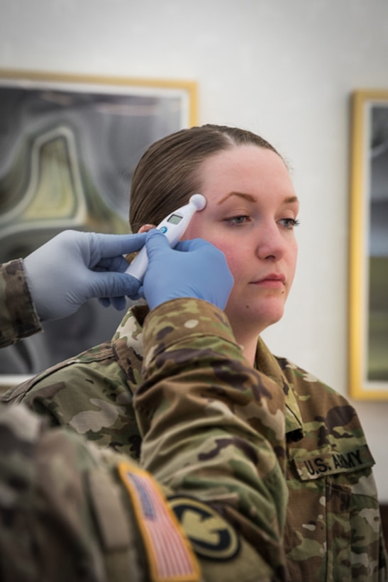 a woman soldier is receives a thermometer test at a National Guard facility