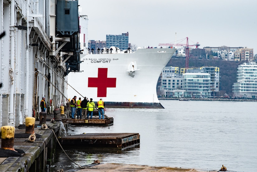 The USNS Comfort moves though the water and approaches the pier where it will dock.