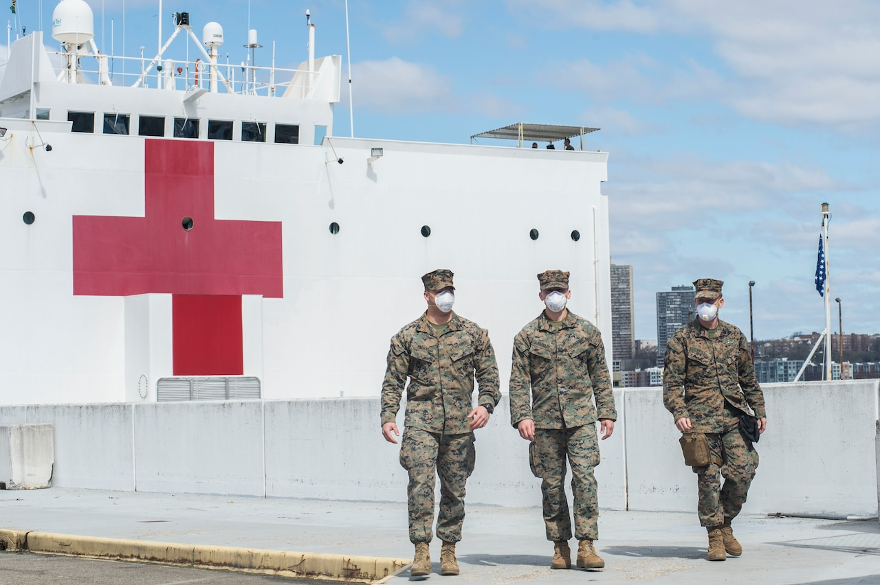 Three service members walk alongside each other, each wearing a face mask. In the background is a navy ship with a large red cross on its side.