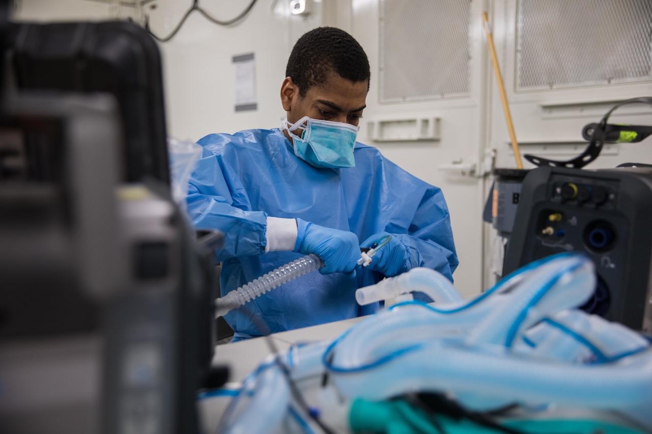 A man in hospital scrubs configures medical equipment.