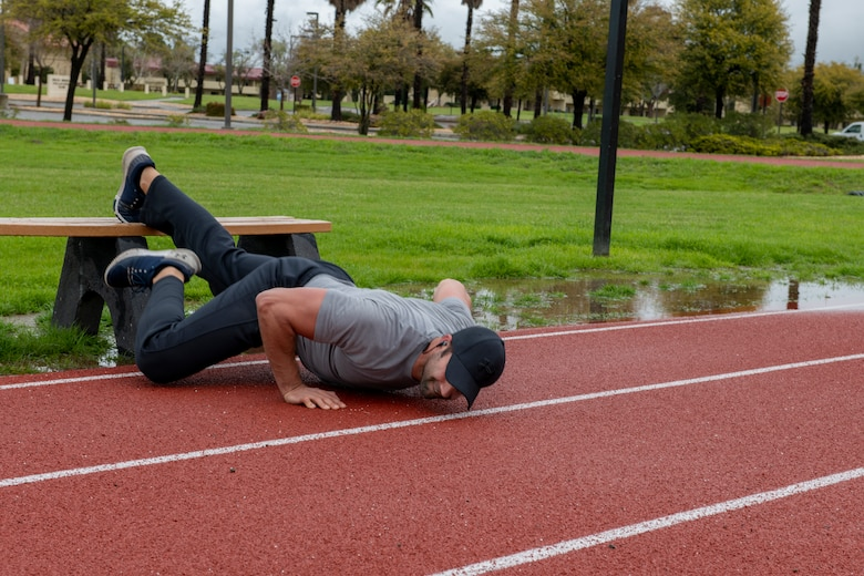 An Airman is doing push ups on a track.