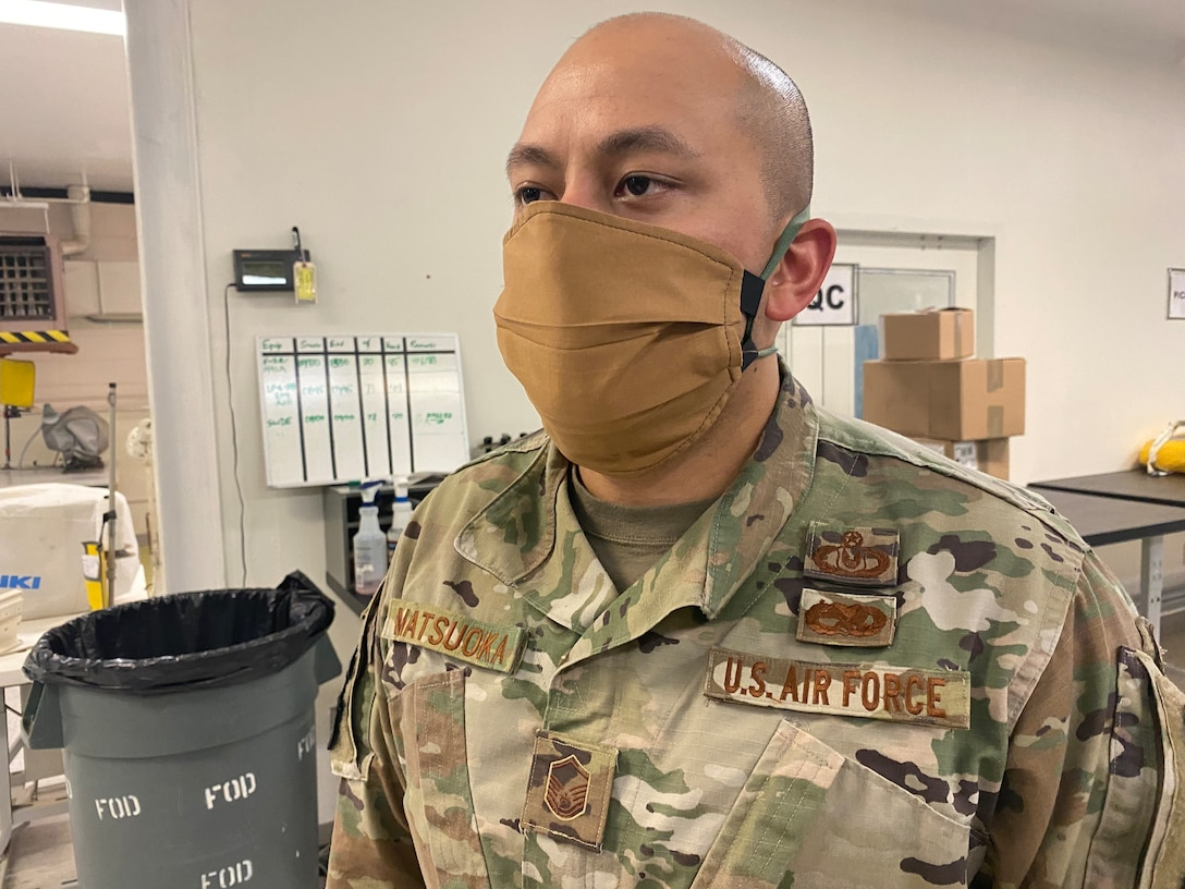 Master Sgt. Henry Matsuoka, section chief, air crew flight equipment, 412th Operations Support Squadron, 412th Operations Group, 412th Test Wing, demonstrates proper use of a mask that was fabricated using available equipment in the Air Crew Flight Equipment section at Edwards Air Force Base, April 7. Although cloth masks don't offer full protection from COVID-19, the CDC advises that a simple cloth covering can slow the spread of the virus and help people who may have the virus and not know it from spreading it to others. (Courtesy photo)