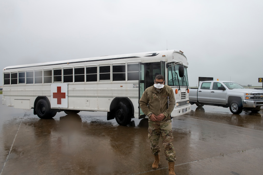 An Airman stands outside of a bus.