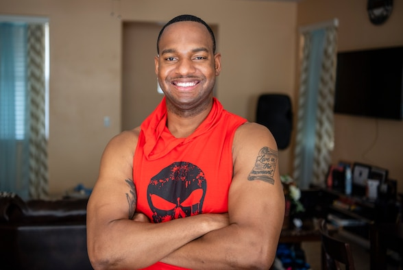 A U.S. Air Force chaplain poses in red and black workout attire at his home.
