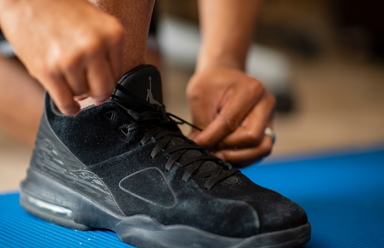 Staff Sgt. Kevin ties his black shoes on a blue work out mat inside his home in Las Vegas.