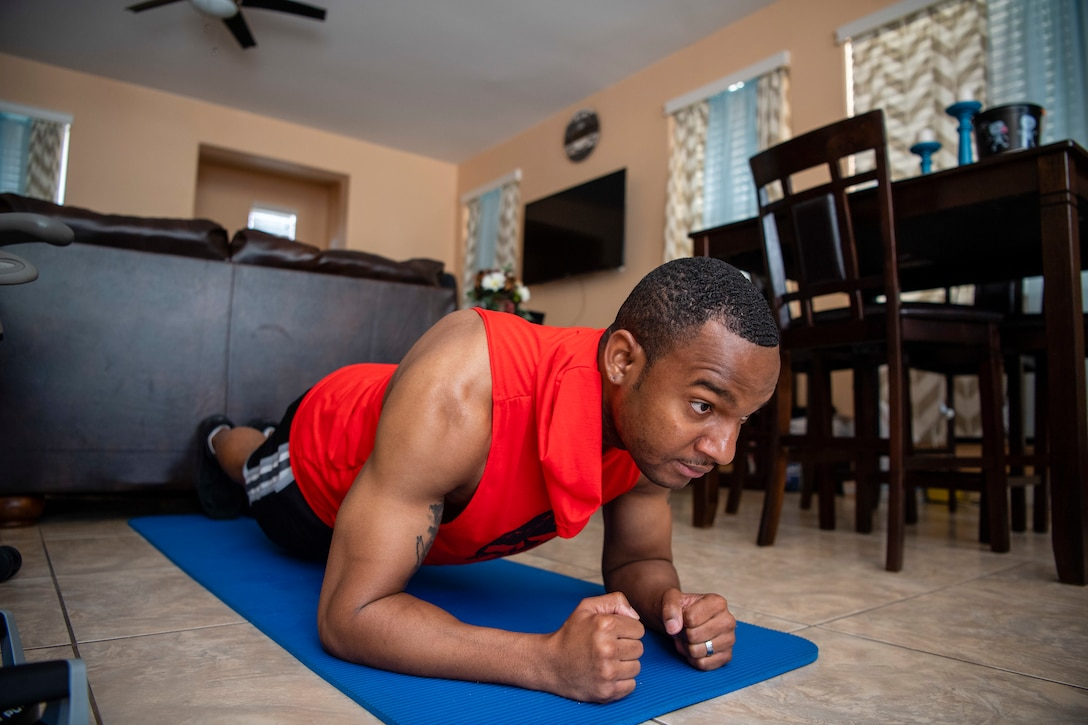 Staff Sgt. Kevin assumes a planking elbow position on a blue workout yoga mat at his home in Las Vegas.