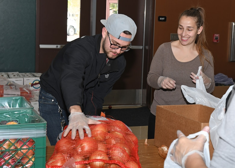 Senior Airman Ethan Morales, 9th Maintenance Squadron aerospace propulsion technician, helps place a bag of onions on a table at a local elementary school in Olivehurst, California, April 6, 2020. The onions will be packaged into a bag that will be distributed to local students. (U.S. Air Force photo by Airman 1st Class Luis A. Ruiz-Vazquez)