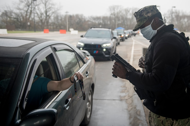 A service member wearing a cloth mask scans an ID card at an entry control point while a line of traffic waits to enter the installation.