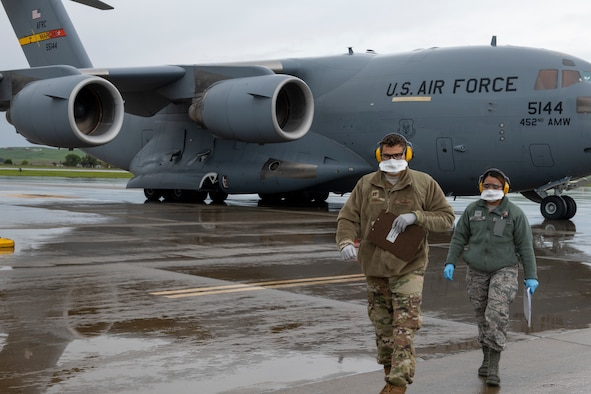 Airmen walk away from a C-17.