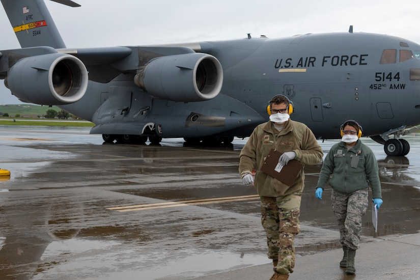Two airmen wearing protective masks walk away from a large transport jet.