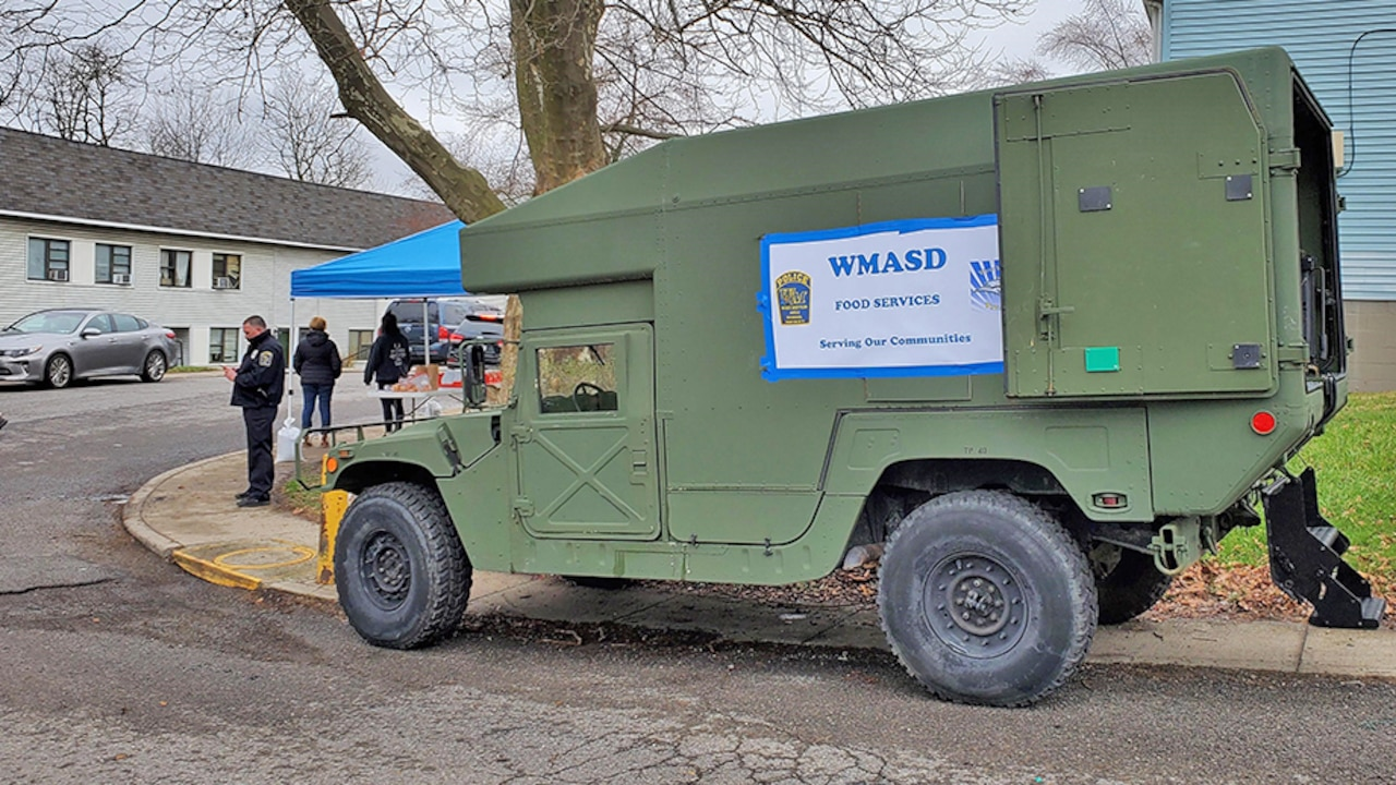 A parked former military vehicle carries a sign that it is being used as a food service truck.