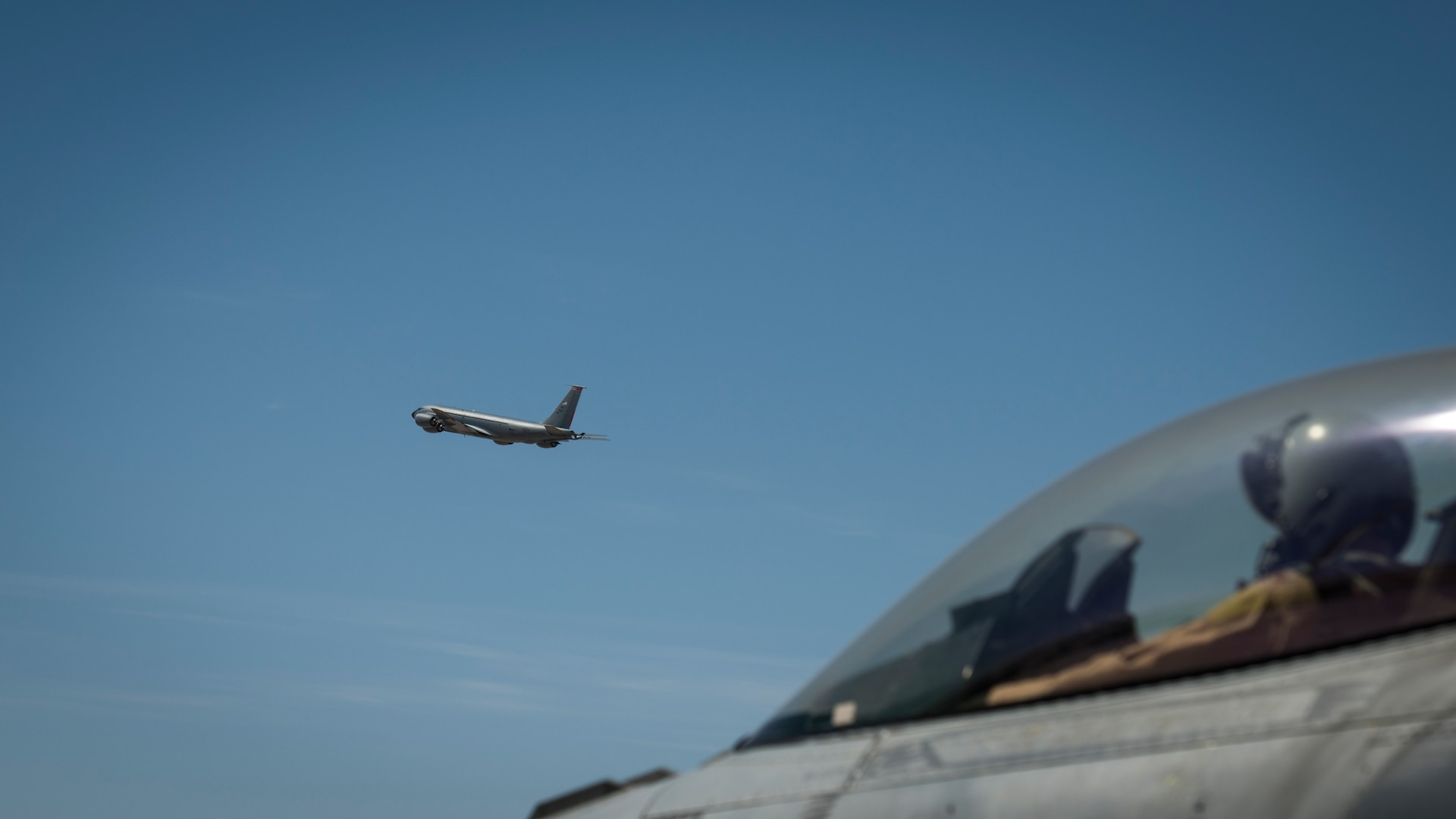 """A U.S. Air Force F-16 """"Viper"""" Fighting Falcon pilot assigned to the 79th Expeditionary Fighter Squadron looks on as a U.S. Air Force KC-135 Stratotanker takes off at an undisclosed location in the U.S. Central Command area of responsibility, Feb. 24, 2020."""