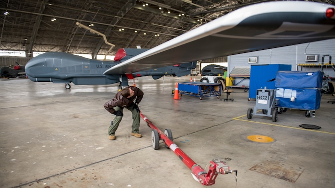Maj. Marc Nichols, 452nd Flight Test Squadron Assistant Director of Operations, conducts a walk-through inspection of an RQ-4 Global Hawk remotely-piloted aircraft at Edwards Air Force Base, California, April 6. (Air Force photo by Giancarlo Casem)