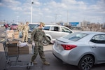 Indiana National Guard troops from the 381st Military Police Company, Plymouth, load groceries into cars of local families at a drive-thru food drive at the Food Bank of Northwest Indiana, Merrillville, Indiana, April 3, 2020.