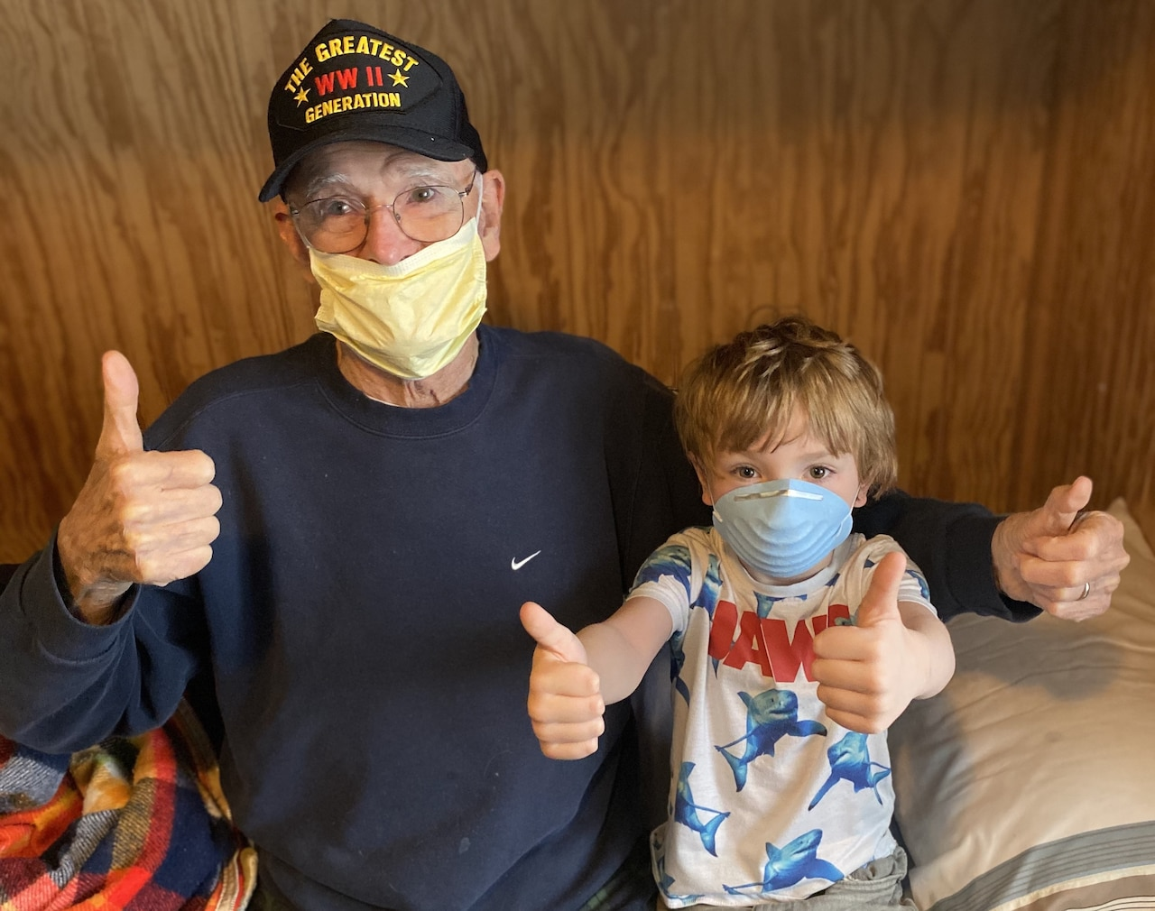 An elderly man and a small boy wearing medical masks give four thumbs up while sitting on a bed.