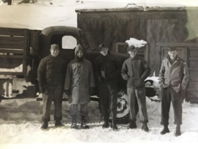 Five World War II Army soldiers stand in the snow in front of an old truck and a small building.