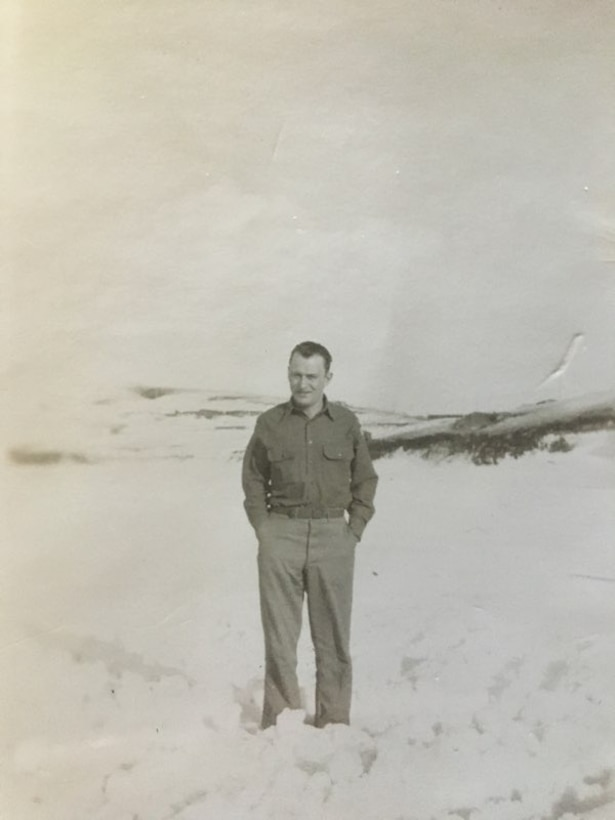 A man in an Army uniform stands outside in the snow.