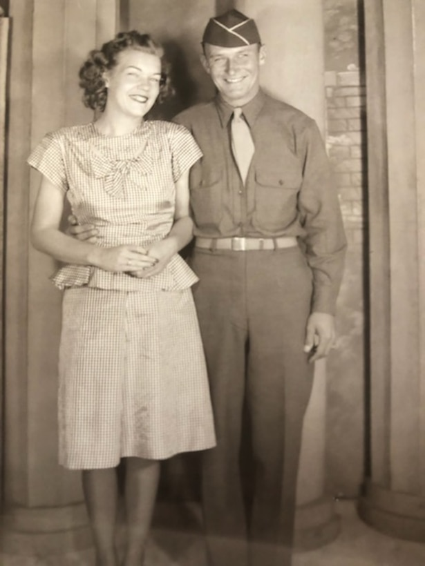 A woman and a man in an Army uniform during the 1940s smile for the camera.