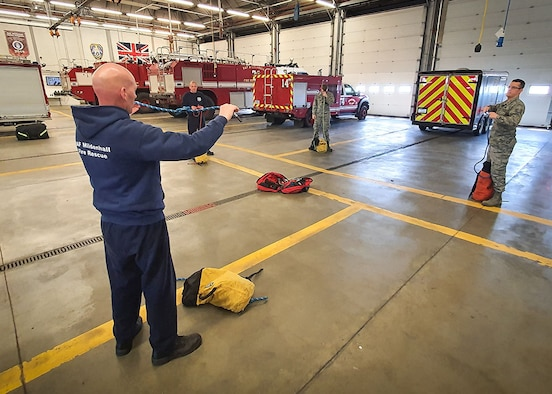 U.S. Air Force and civilian firefighters from the 100th Civil Engineer Squadron Fire Department carry out a rescue rope inspection while practicing physical distancing April 7, 2020, at RAF Mildenhall, England. During the COVID-19 lockdown, the firefighters are taking extra precautions both in and out of the fire station to ensure the health and safety of both themselves and the base community. (Courtesy photo by Matthew Thorpe)