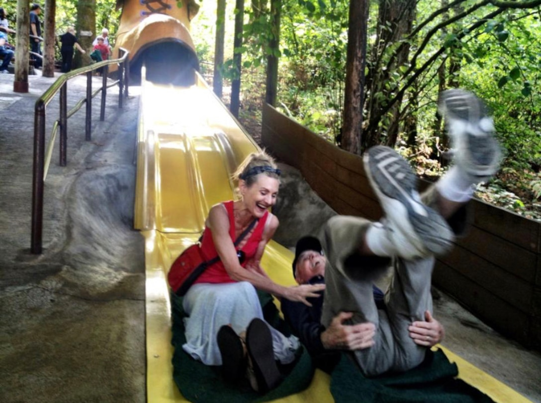 A woman and an elderly man laugh after sliding down a large, two-person slide.