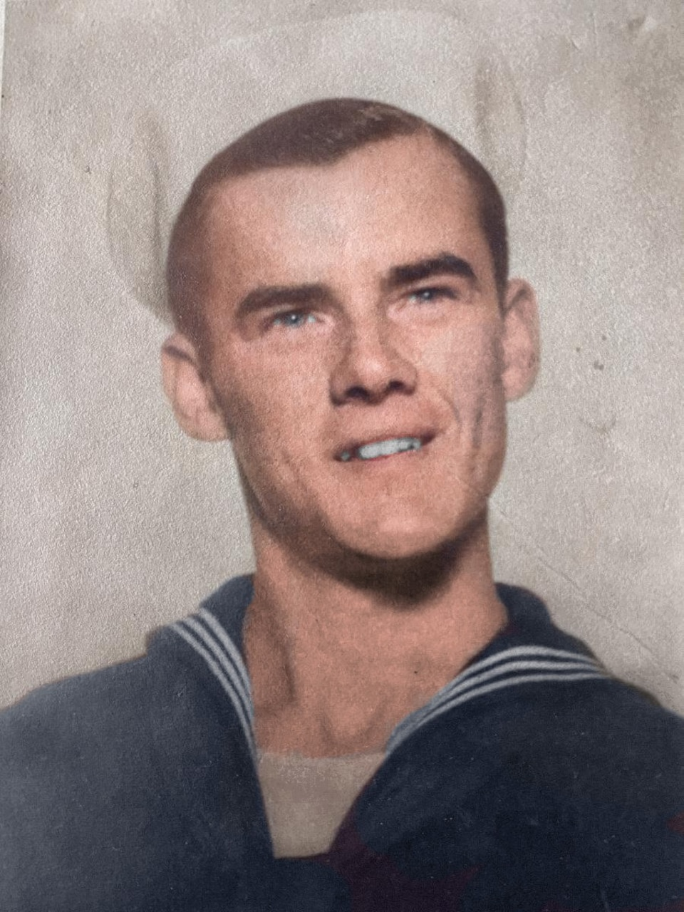 A young sailor in dress uniform smiles for an official photo.