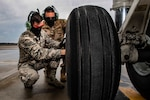 Air Force Senior Airman Zachary Anderson and Staff Sgt. Michael Zitelli perform a basic post-flight operations inspection on a C-17 Globemaster III while wearing personal protective equipment at the Pittsburgh International Airport Air Reserve Station, April 7, 2020.