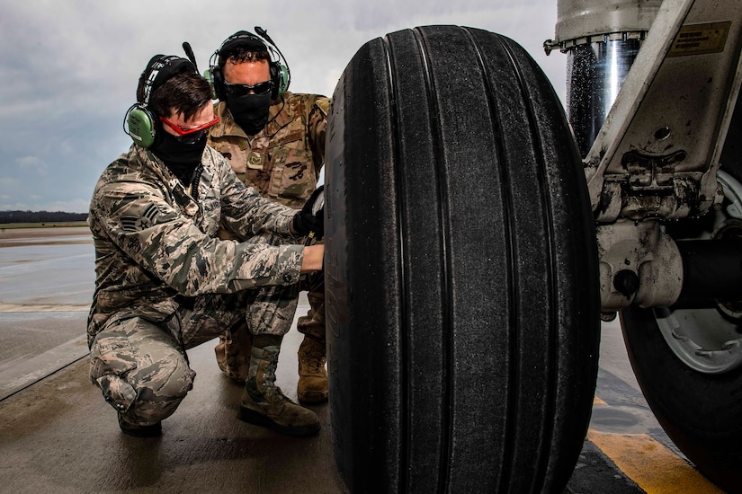 Two airmen wearing face masks kneel next to a large tire.