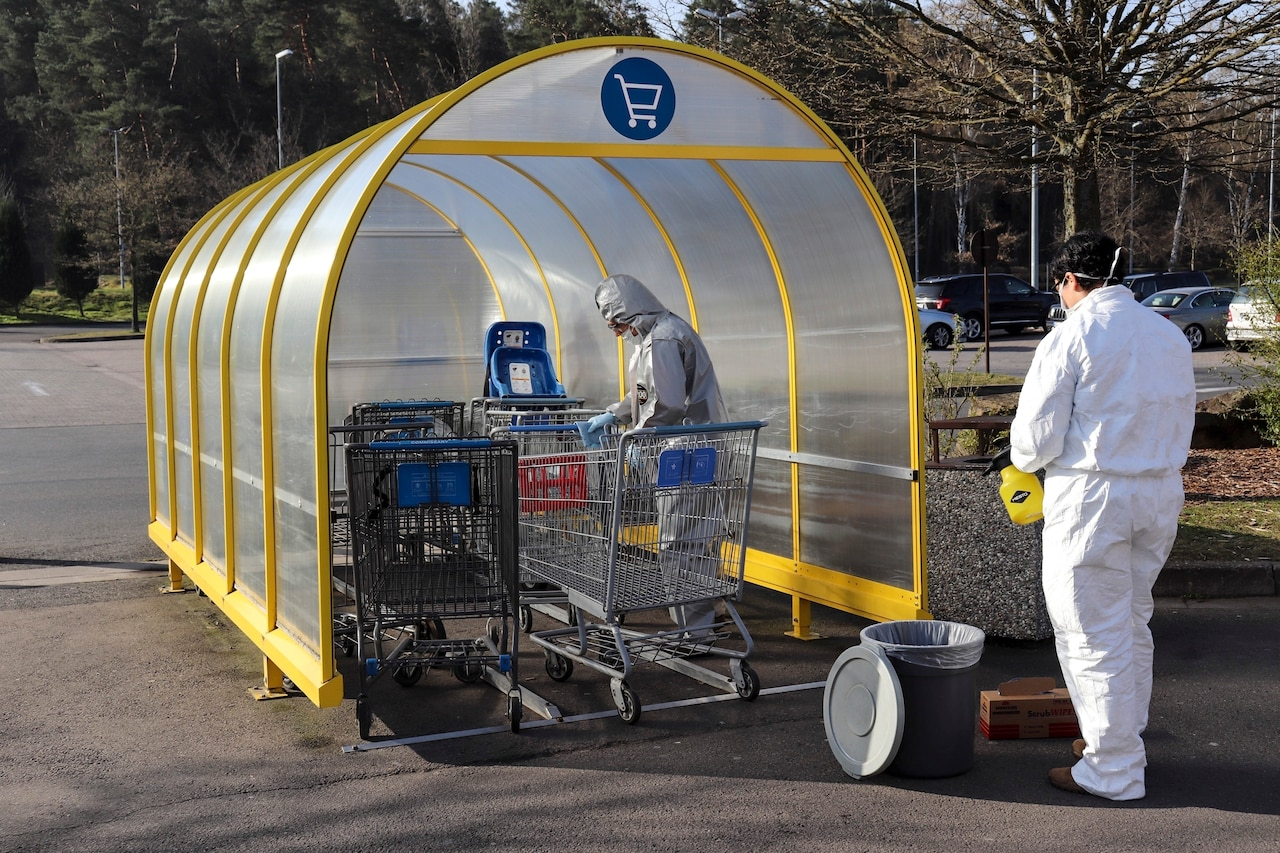Two soldiers in white protective outfits work to clean grocery carts in a parking lot.