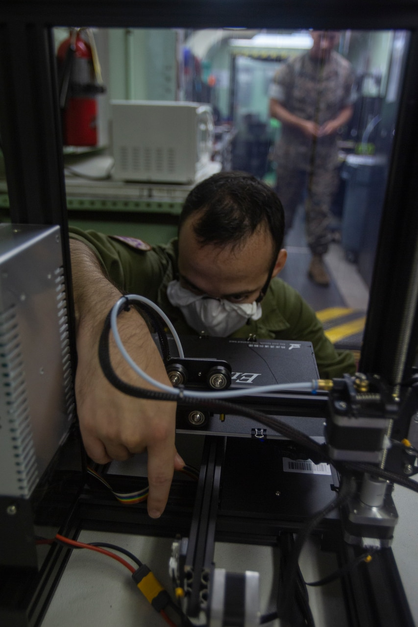 A Marine wearing a facemask performs maintenance on a 3D printer.