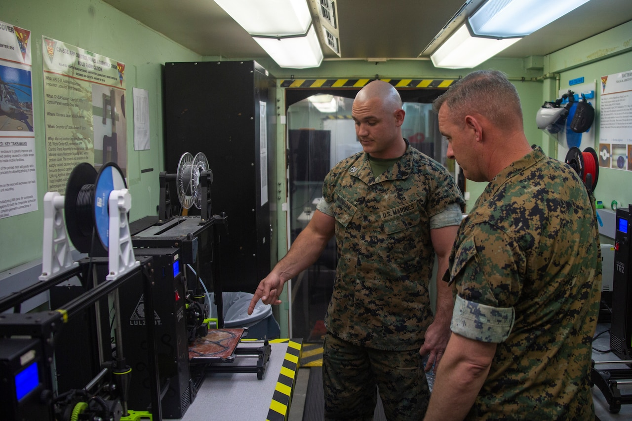 A Marine Corps staff sergeant briefs a Marine Corps major on a 3D printer's operation.