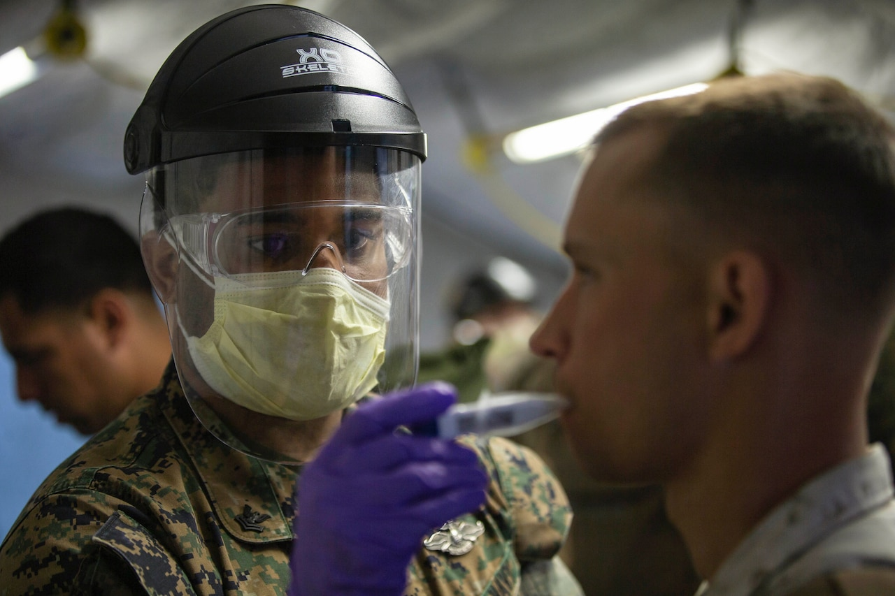 A sailor in protective gear takes a Marine's temperature.