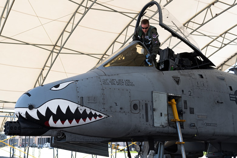 A photo of a pilot cleaning the windscreen of an A-10C Thunderbolt II
