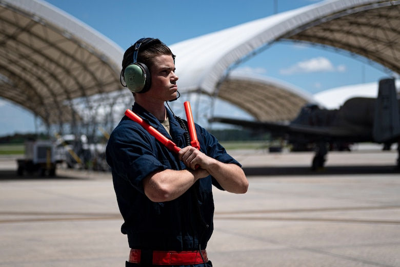 A photo of an Airman marshaling an aircraft.