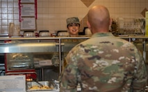 Airman serves food to another Airman in a lunch line.