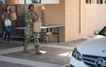 Airman and Civilian worker hand out to-go lunch order.
