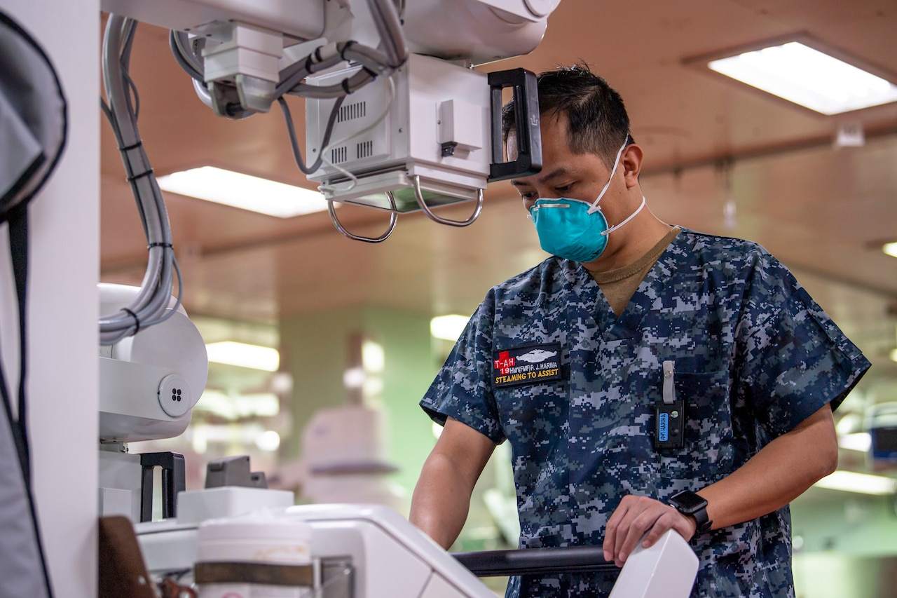 A service member wearing a paper face mask operates a piece of medical equipment.