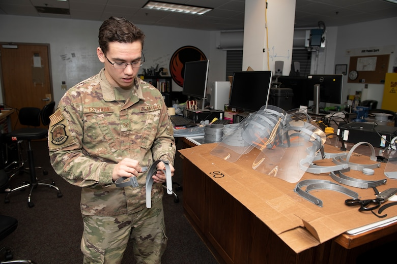 U.S. Air Force Staff. Sgt. Maximilion Estrada, Phoenix Spark noncommissioned officer in charge of agile manufacturing, assembles a face shield, April 6, 2020, at Travis Air Force Base, California. The 60th Air Mobility Wing Phoenix Spark innovation cell has been working with other base organizations, the 60th Aerospace Medicine Squadron bioenvironmental engineering flight and the 60th Maintenance Squadron fabrication flight, since the beginning of March to deliver innovative personal protective equipment to Airmen amidst COVID-19. (U.S. Air Force photo by Senior Airman Jonathon Carnell)
