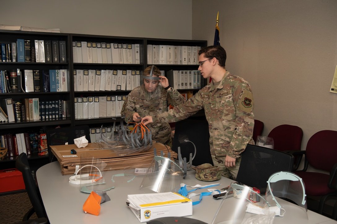 U.S. Air Force Staff. Sgt. Maximilion Estrada, right, Phoenix Spark noncommissioned officer in charge of agile manufacturing, discusses newly prototyped face shields with Staff Sgt. Kimber Keaton, 60 Medical Group Bioenvironmental Engineer craftsman, April 6, 2020, at Travis Air Force Base, California. The 60th Air Mobility Wing Phoenix Spark innovation cell has been working with other base organizations, the 60th Aerospace Medicine Squadron bioenvironmental engineering flight and the 60th Maintenance Squadron fabrication flight, since the beginning of March to deliver innovative personal protective equipment to Airmen amidst COVID-19. (U.S. Air Force photo by Senior Airman Jonathon Carnell)