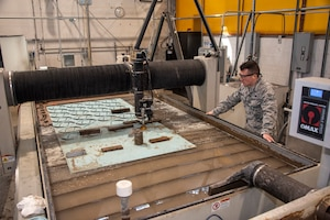 U.S. Air Force Senior Airman Robert Lee Prankard, 60th Maintenance Squadron aircraft metals technician, monitors a water jet as it cuts through old aircraft material to create parts for face shields March 31, 2020, at Travis Air Force Base, California. The 60th Air Mobility Wing Phoenix Spark innovation cell, 60th MXS and 60th Bioenvironmental Engineering Squadron collaborated to come up with easy-to-manufacture PPE for David Grant USAF Medical Center personnel. (U.S. Air Force photo by Tech. Sgt. Traci Keller)