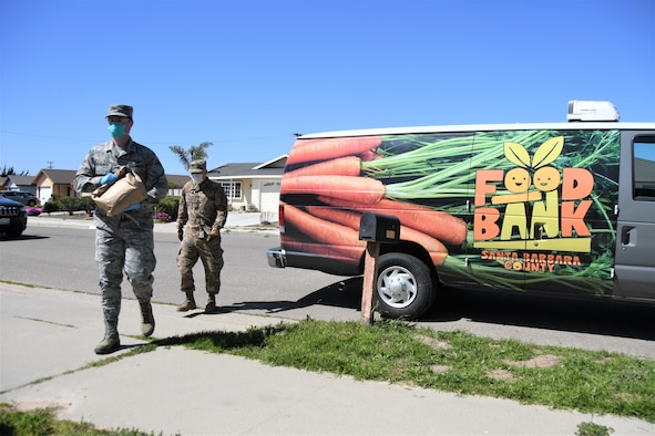 Airman 1st Class Soren Dietrichson, front, and Staff Sgt. Travis Emery, space operators for the California Air National Guard's 216th Space Control Squadron, deliver food to residences in Orcutt, California, on April 2, 2020, as part of the Cal Guard's COVID-19 humanitarian mission.