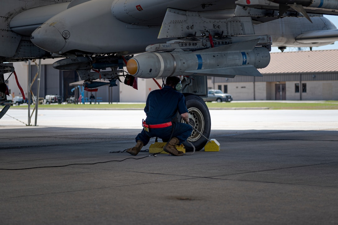 A photo of an Airman pulling chocks from an A-10C Thunderbolt II