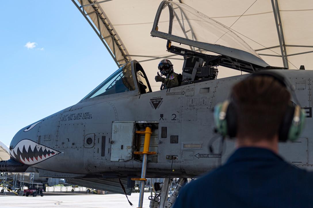 A photo of a pilot giving an Airman a thumbs-up