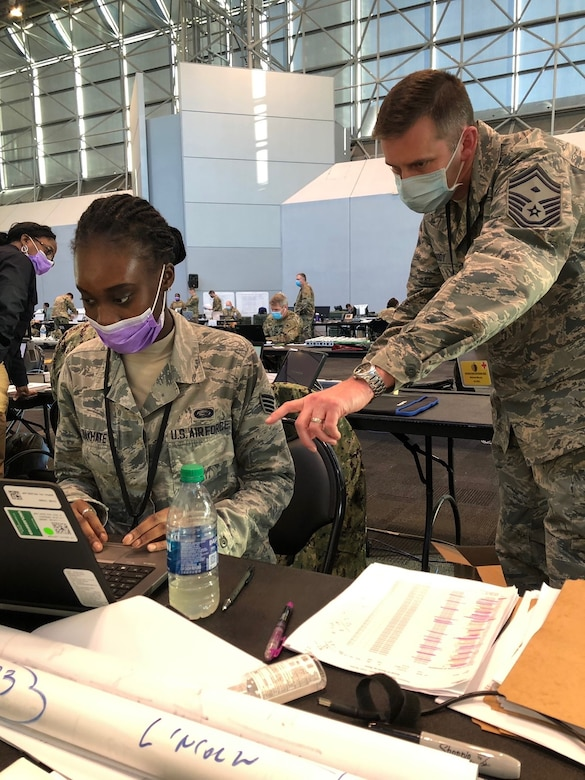 Senior Master Sgt. Michael B. Moody, 64th AEG first sergeant, oversees Staff Sgt Awa B. Diakhate, 64th AEG PERSCO, April 8, 2020. They were both forward deployed to the Javits Center in NYC to help fight against COVID-19.