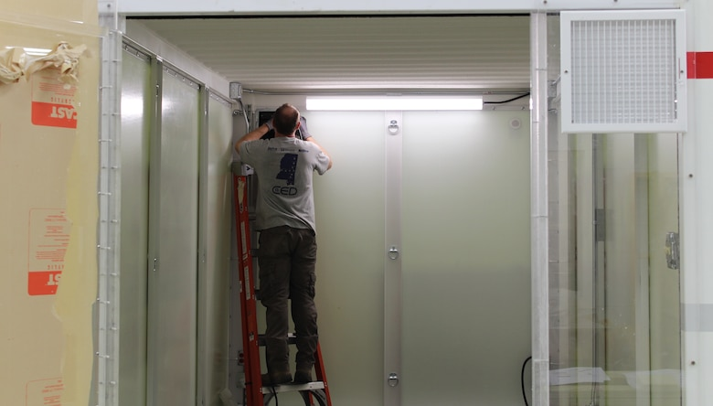 Employees from the U.S. Army Engineer Research and Development Center's Directorate of Public Works hang a door on a makeshift hospital room, or Containerized Medical Solution, constructed of wood and a metal frame, March 31, 2020. The team has been tasked with building out designs developed by the USACE Hunstville District and assessing their feasibility. The team is working to examine converting a portable storage unit into a one-bed hospital room versus constructing a wooden and metal room from scratch for the emergency response to the COVID-19 outbreak.
