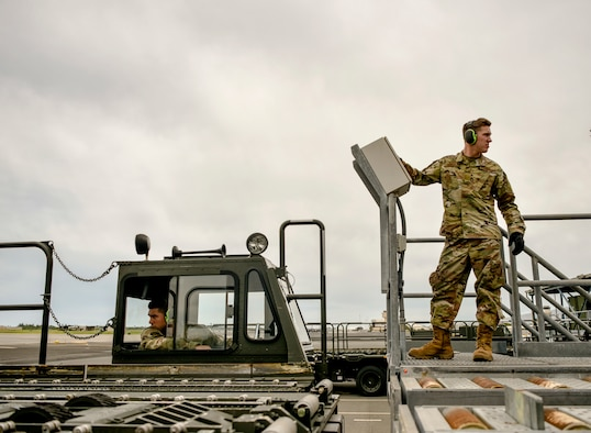 U.S. Air Force Senior Airman Mario Garcia and Airman Basic Brock Dowell, 735th Air Mobility Squadron air freight personnel,  load cargo on and off of a Tunner 60K loader into a dock at Joint Base Pearl Harbor-Hickam, Hawaii, March 31, 2020. The 735th AMS supports global airlift in the Indo-Pacific area. (U.S. Air Force photo by Tech. Sgt. Anthony Nelson Jr.)